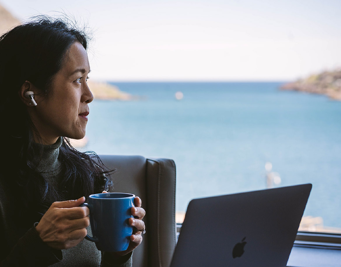 A woman drinking coffee while working on a laptop